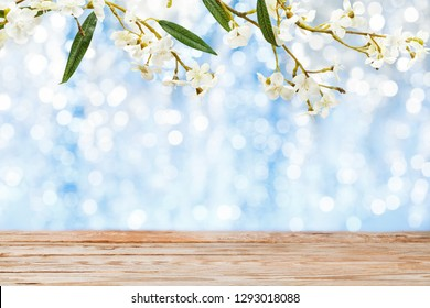 Empty wooden table and peach blossom over festive bokeh background. Easter holiday concept
