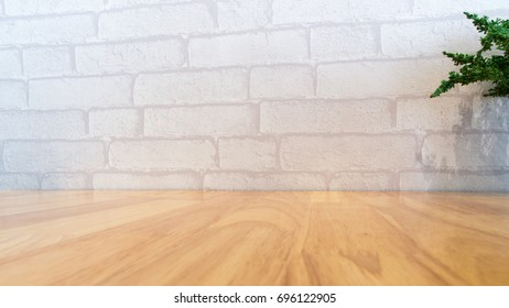 Empty wooden table with a plant on the white brick room for montage product display