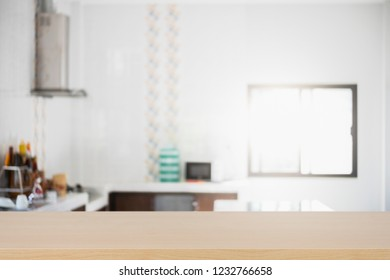 Empty wooden table platform blur kitchen background for presentation product.