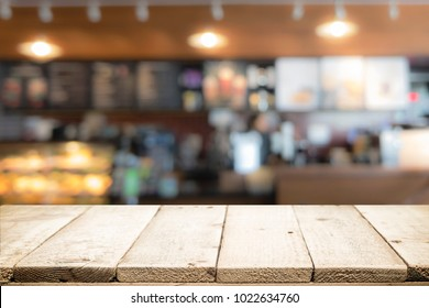 Empty wooden table for present product on coffee cafe or soft drink counter bar blur background with bokeh image.