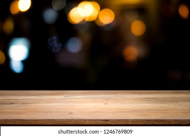 Empty wooden table for present product on bokeh at night blur background with bokeh image.