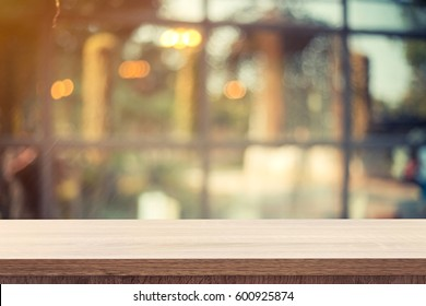 Empty wooden table for product or montage display and blurred coffee shop backdrop.