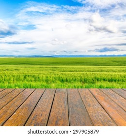 Empty wooden table for product presentation. In the background blurred wheat field