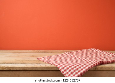 Empty wooden table with red checked tablecloth over red wall  background