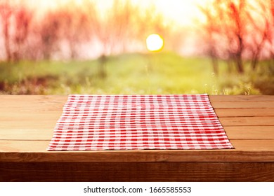 Empty wooden table with a red tablecloth