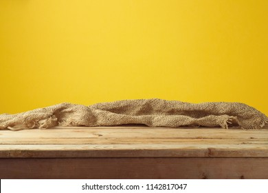 Empty wooden table with sackcloth over yellow wall  background