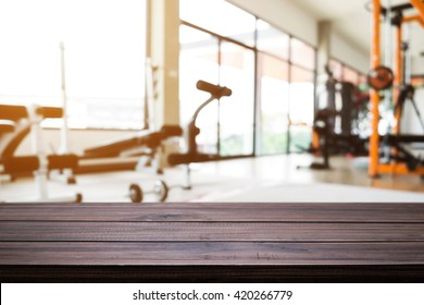 Empty wooden table space platform with fitness gym background. For product display montage.