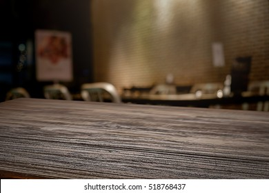 Empty wooden table space platform and blurred outdoor restaurant background for product display montage.