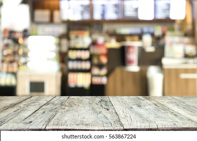 Empty wooden table space platform and blurred bakery shop or coffee cafe background for product display montage.