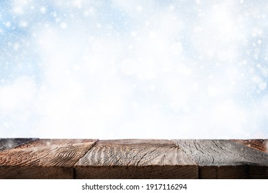 Empty wooden table surface ove blue winter background with snow. Template for product display