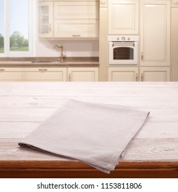 Empty wooden table with tablecloth near the window in kitchen. White Napkin close up top view mock up for design. Kitchen rustic background.
