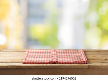 Empty wooden table with tablecloth over abstract bokeh background. Mock up for display or montage product