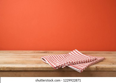 Empty wooden table with tablecloth over red wall  background