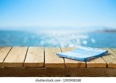 Empty wooden table with tablecloth over sea beach background