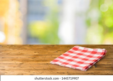 Empty wooden table with tablecloth over abstract bokeh background