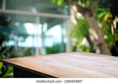 empty wooden table top with blur coffee shop or restaurant in green garden background .