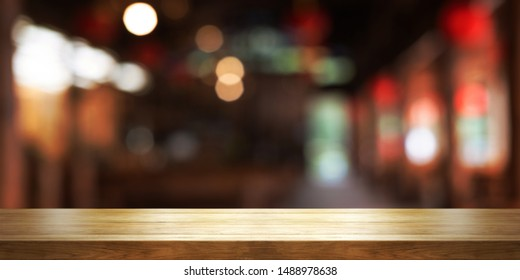 Empty wooden table top with blur coffee shop or restaurant interior background, Panoramic banner. Abstract background can be used for display or montage your products.