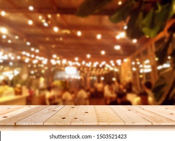Empty wooden table top with blur coffee shop or restaurant interior background