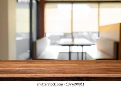 Empty wooden table top with blur background of office and meeting room.