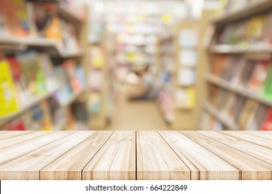 Empty wooden table top with Blur bookshelves in bookstore background. can be used product display.