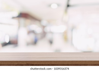 Empty wooden table top with blurred modern shopping mall background for product display and montage.
