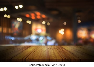 Empty wooden table top with blurred coffee shop interior background. can be used product display.