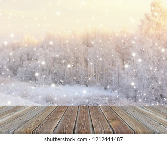 Empty wooden table top on blurred winter backdrop. Empty space for Your object. Background, layout with winter trees and snowflakes.