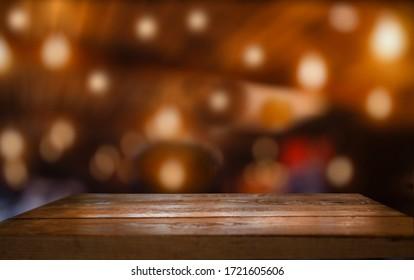 Empty wooden table top on blur light golden bokeh of cafe restaurant, bar in a dark background.