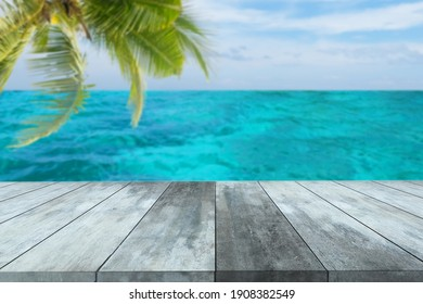 Empty wooden table top stands for product dispaly or montage in advertisement with blurred turquoise sea and blue sky background.