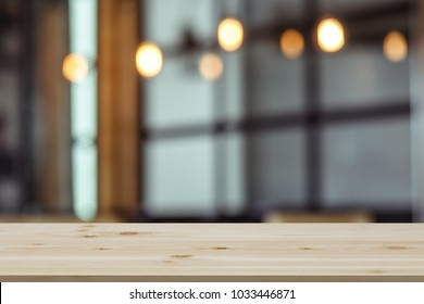 Empty wooden table top with view of room or wooden desk with restaurants with blur background, copy space for your text
