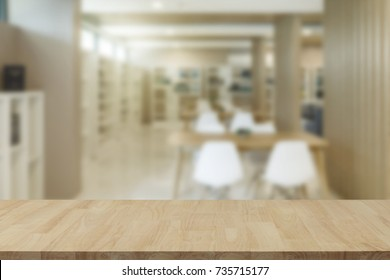 Empty wooden table top with view of office or wooden desk with library room with blur background, copy space for your text