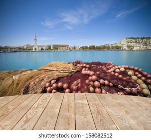 Empty wooden tabletop and fishing net with harbor in the background - ideal base for seafood