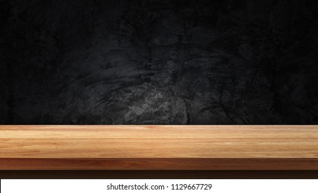 Empty wooden tabletop isolated on dark background. For your product placement or montage with focus to the table top in the foreground. Empty wooden shelf
