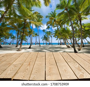 Empty wooden tabletop for Your product advertisement. Tropical beach in Caribbean sea at Saona island in the background, Dominican Republic