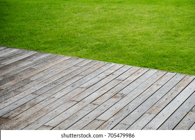 empty wooden terrace with green lawn