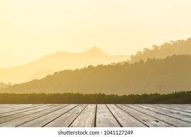 Empty wooden terrace with Layers of mountain ridges silhouettes on background