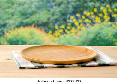 Empty wooden tray on table over blur trees with bokeh background, for food and product display montage