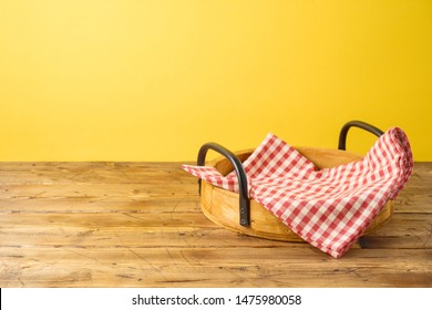 Empty wooden tray with red checked tablecloth on wooden table over yellow background