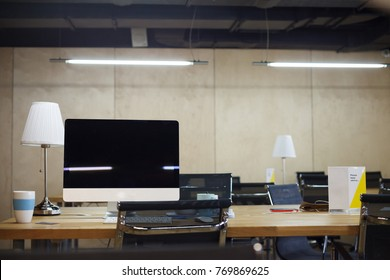 The empty workplace of the director of the company is computer with large monitor, office supplies, chair and lamps against background of beige wall. Co-working. Copy space