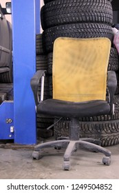 empty workplace at the tire service next to the car lift. auto hoist, old chair, used tires