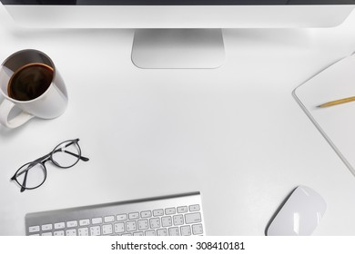Empty workspace on white table. View from above on the clean, well organized working space framed by PC, keyboard, mouse, pencil, coffee cup and glasses