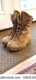Empty, worn, military work boots by a house door. Authentic, realistic, used boots symbolizing someone working hard, or someone no longer there.