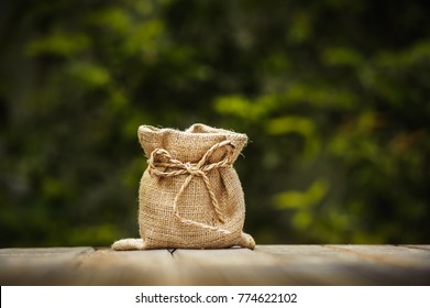 empty woven bag isolate put on wooden table with green leave background
