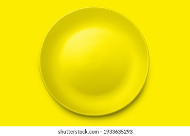 Empty yellow ceramics plate on yellow background with clipping path.