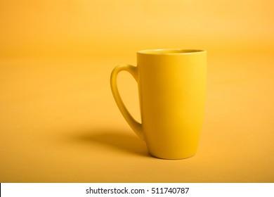 Empty yellow cup on yellow background. Yellow mug empty blank for coffee or tea.