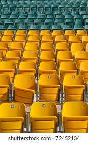 Empty Yellow and Green Stadium Seats, with one of the yellow ones broken.