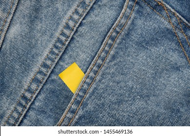 Empty yellow paper stick on blue jeans. copy space used for add messages.