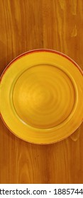 empty yellow plate on a wooden table