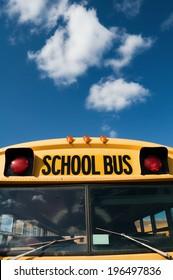 An empty yellow school bus awaits its passengers in the sun.