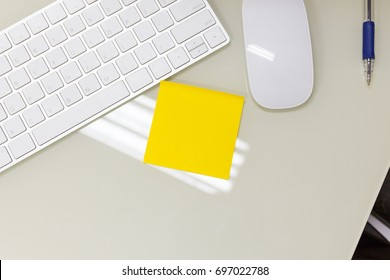 A Empty yellow sticky note on work business desk.
